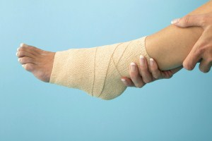 Woman Holding Bandaged Ankle --- Image by © Royalty-Free/Corbis